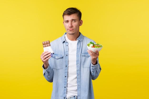 健康的なライフスタイルと人々の感情の概念。ボウルとキャンディーバーでサラダを見せて、嫌がるダイエット食品を食べるように顔をゆがめ、黄色の背景に立っている暗いハンサムな白人の男