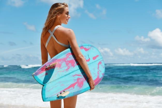 健康的なライフスタイルとレクリエーションの概念。屈託のない女性の背面図は、水着とサングラスを着用し、しんみりと海に見え、サーフボードを運んでおり、夏のスポーツ活動が好きです。ビーチの女性