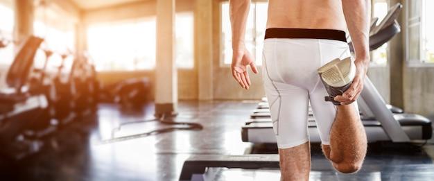 健康的なライフスタイルとリラクゼーション。ジムフィットネスでトレーニングの前に脚の温暖化を伸ばして筋肉のハンサムな男の後ろ。