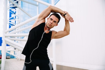 Healthy lifestyle and sport concept. Handsome concentrated man doing stretching exercises
