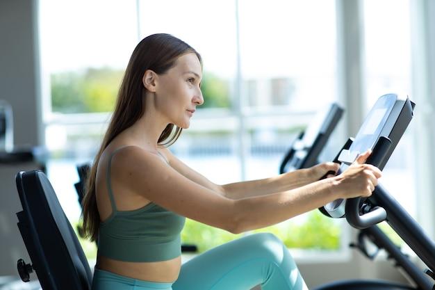 건강한 라이프 스타일과 스포츠 개념. 체육관에서 자전거 훈련 매력적인 젊은 여자.