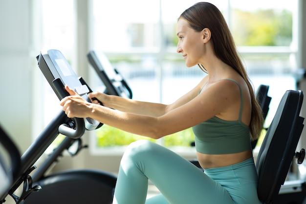 Концепции здорового образа жизни и спорта. привлекательная тренировка молодой женщины на велосипеде в тренажерном зале.
