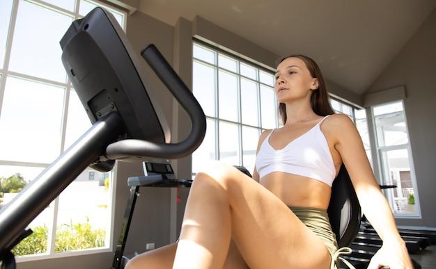 건강한 라이프 스타일과 스포츠 개념. 체육관에서 자전거에 훈련하는 젊은 여자.