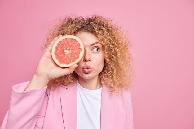 健康的なライフスタイルとビタミン。素敵な女性は巻き毛のふさふさした髪を保ち、唇を折りたたんで目を覆い、グレープフルーツの半分はピンクの壁の空白スペースに隔離されたフォーマルな服を着てダイエットを続けます