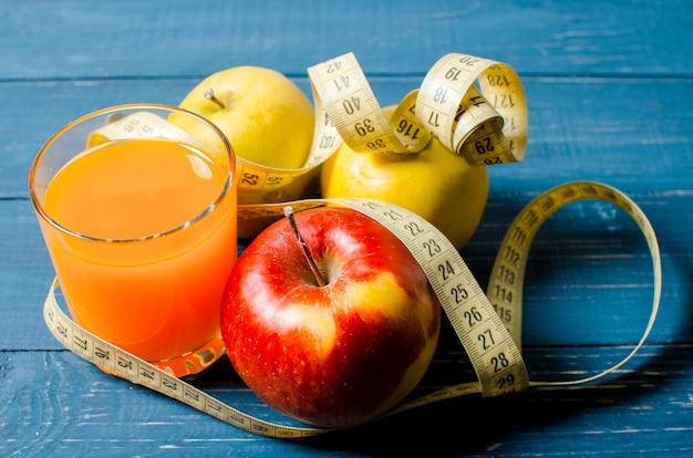 Здоровый образ жизни. яблочный и апельсиновый сок на деревянном столе