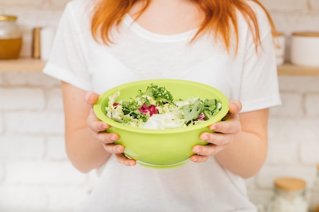 건강한 생활. 균형 잡힌 식단과 체중 감량 레시피. 유기농 성분. 혼합을 들고 여자는 샐러드 그릇을 떠난다.