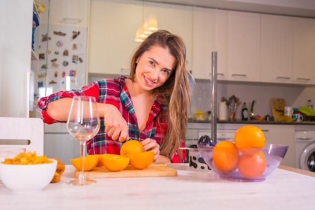 健康的なライフスタイル、彼女の台所で朝食に新鮮なオレンジジュースを持っている金髪の白人女性