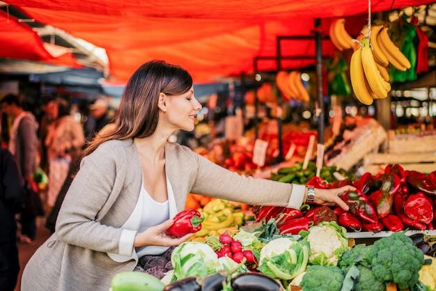 健康的な生活様式。魅力的な女性は農民市場で野菜を買う。