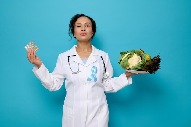 Healthy lifestyle choices, proper nutrition or medication treatment for diabetes awareness day concept. pretty female doctor holds plate with healthy raw food and blister with medical pills in hands