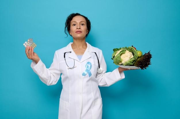 健康的なライフスタイルの選択、糖尿病啓発デーのコンセプトのための適切な栄養または投薬治療。きれいな女性医師が手に健康的な生の食品と水ぶくれと医療の丸薬でプレートを保持します