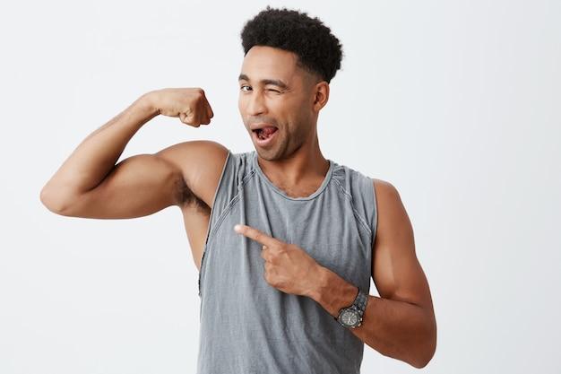 健康的な生活様式。腕の筋肉を示すスポーティな灰色のシャツに巻き毛を持つ若いセクシーな浅黒い肌の男性の孤立した肖像画を閉じて、それを指して、開いた口でウインクします。