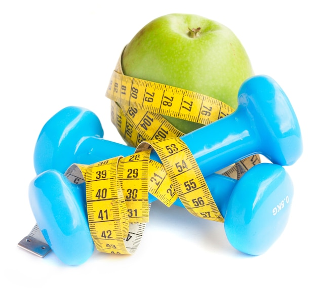 Healthy lifestyle concept  apple with dumbbells and measuring tape