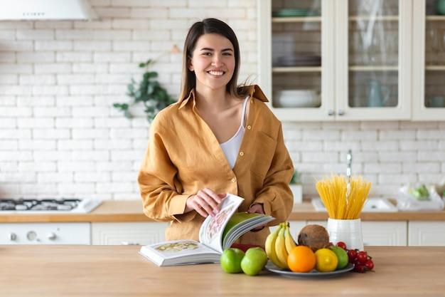 健康的なライフスタイルのコンセプト。健康的な栄養のための食品のセットを持つ美しい若い女性は、台所で家に立っています