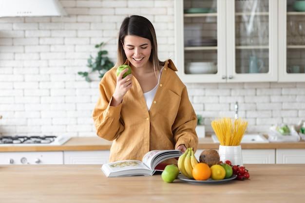健康的なライフスタイルのコンセプト。健康的な栄養と料理本のための食品のセットを持つ白人の美しい若い女性は、キッチンで家に立っています
