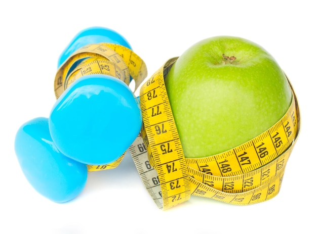 Healthy lifestyle concept  green apple with dumbbells and yellow measuring tape