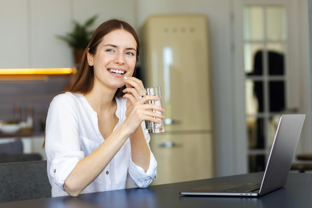 健康的なライフスタイルのコンセプト。コップ一杯の水で幸せな若い白人女性は、ホームオフィスに座って、笑顔で精神的な覚醒または鎮痛剤のためにビタミンを飲みます