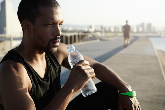 Healthy lifestyle concept. profile portrait of black sportsman with muscular body sitting on pavement in morning sun after training exercises, holding bottle, drinking water, looking into distance