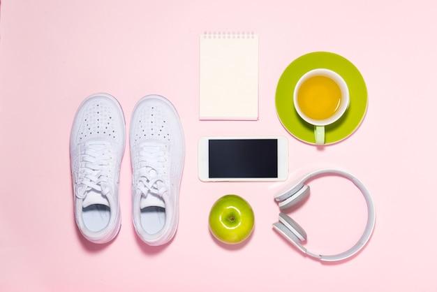 健康的なライフスタイルのコンセプト。パステルカラーの背景にスニーカー、お茶、リンゴ、ヘッドフォン。