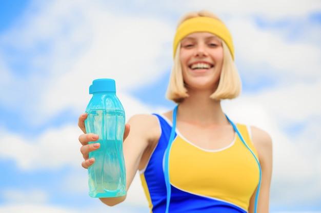 健康的なライフスタイルのコンセプト。スポーツウェアの女性は、水のボトルを保持しています。実行後に水を飲む若い女性。スポーツの女の子は空の背景にボトルから水を飲みます。スポーツ中の飲酒。