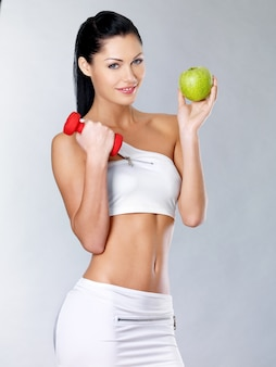 Healthy lifestyle concept for woman stands with green apple.