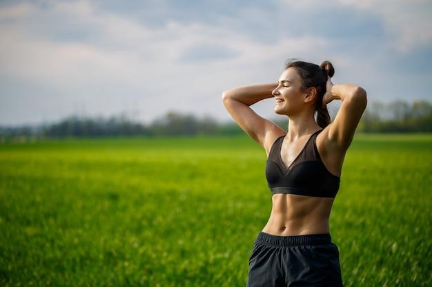 건강한 라이프 스타일 개념입니다. 운동복을 입은 젊은 매력적인 여성은 새벽에 자연에서 훈련하기 전에 손을 뻗습니다. 근육 온난화