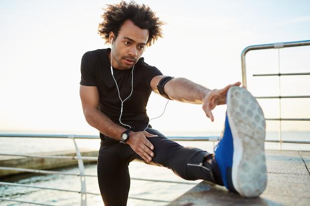 健康的なライフスタイルのコンセプトです。アスレチックボディが桟橋でストレッチし、足をプラットフォームに配置してウォーミングアップする若い黒肌の男性ランナー