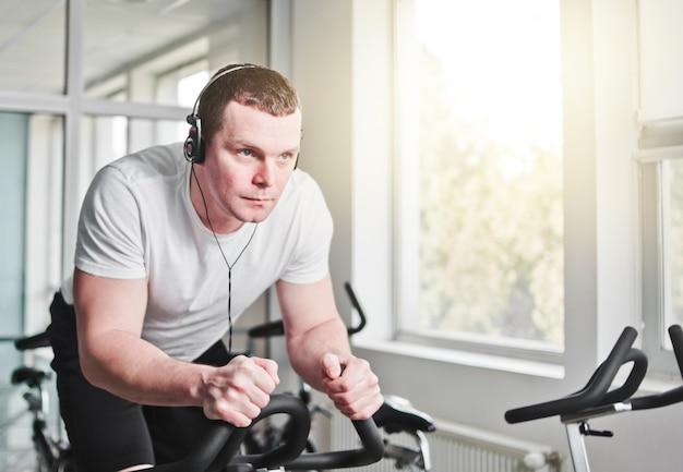 Концепция здорового образа жизни. молодой спортивный мужчина в белой футболке и шортах тренирует велосипед в классе спиннинга. кардио тренировки