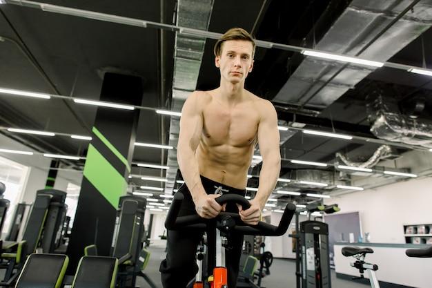 Концепция здорового образа жизни. молодой спортивный человек без рубашки осуществляет велосипед на спиннинг класса. кардио тренировка. молодой человек спорта ехать неподвижный велосипед в спортзале фитнеса.