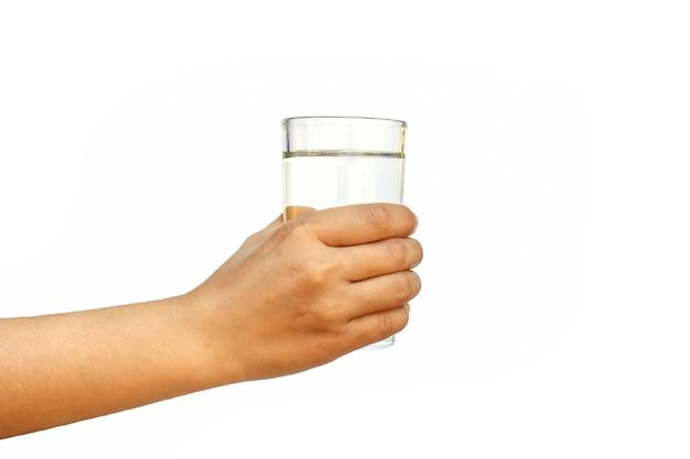 健康的なライフスタイルの概念。白い背景で隔離の透明な水ガラスを保持している若い女性。