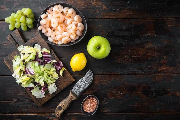 Здоровый образ жизни - приготовление свежего салата из креветок, зеленого салата, оливкового сервиза, с яблочно-виноградным соусом, на старом темном деревянном столе, плоская планировка, вид сверху
