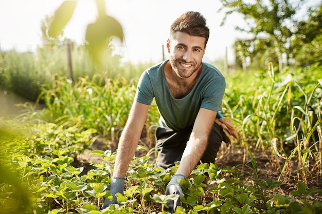 Здоровый образ жизни. сельская жизнь. крупным планом портрет молодого привлекательного бородатого кавказского фермера, проводящего утро в саду возле дома, сбора урожая