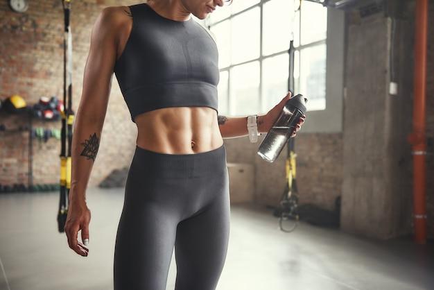 健康的なライフスタイルは、水のボトルを保持しているスポーツウェアの若い運動女性の写真をトリミングしました