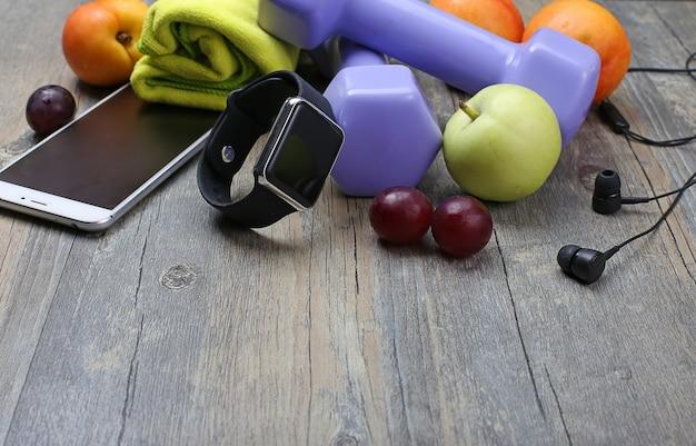 健康的なライフスタイルのダンベルスマートな時計と果物