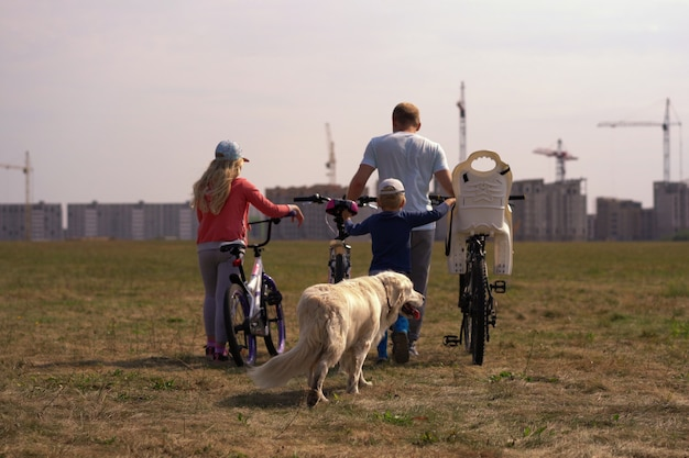 Healthy lifestyle - family with bicycles and a dog walking along the field near the city