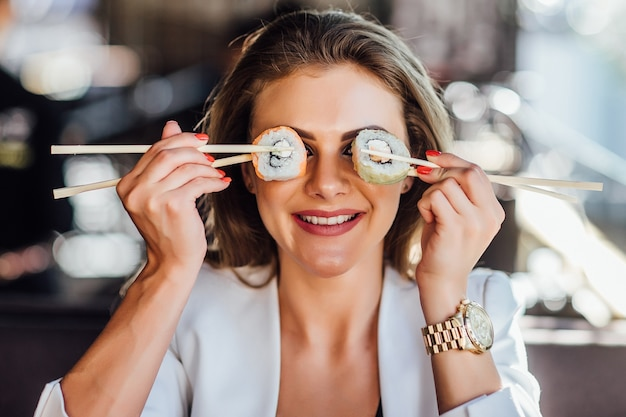Stile di vita sano modello femminile sorridente felice tenendo le bacchette sugli occhi.