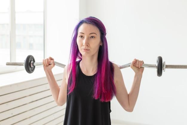健康的なライフスタイル、フィットネス、人々、スポーツのコンセプト-ボディバーと黒のシャツのトレーニングでフィットする女性の肖像画をクローズアップ