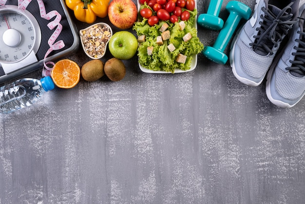 Healthy lifestyle, food and sport accesories on gray