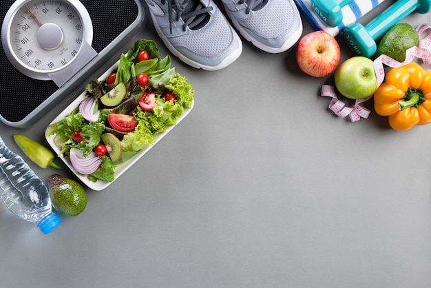 Healthy lifestyle, food and sport concept on gray.