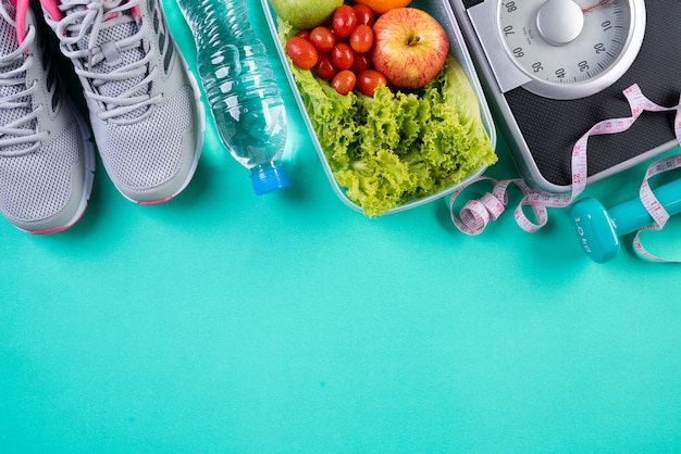 Healthy lifestyle, food and sport concept on green pastel.