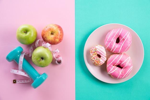 Healthy lifestyle, food and sport concept on pink blue pastel.