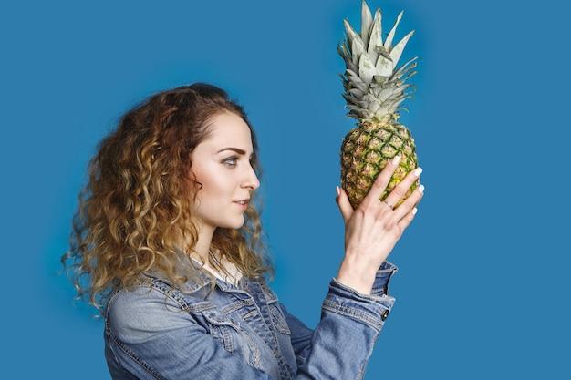 Stile di vita sano, fruttarismo, estate, dieta, cibo e concetto di nutrizione. ritratto laterale della giovane femmina caucasica alla moda con capelli ondulati che sceglie l'ananas dolce maturo per la macedonia