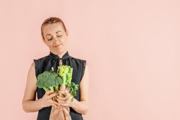 Здоровый образ жизни. девушка держит в руках брокколи и зеленые овощи, розовая стена. диета и правильное питание. ,