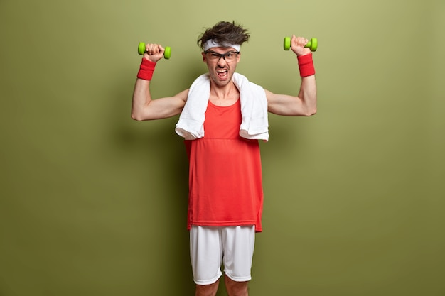 Healthy lifestyle and gym exercising. determined man raises dumbbells for strong muscles, puts all efforts in gaining positive result, dressed in sportswear with towel around neck, isolated on green