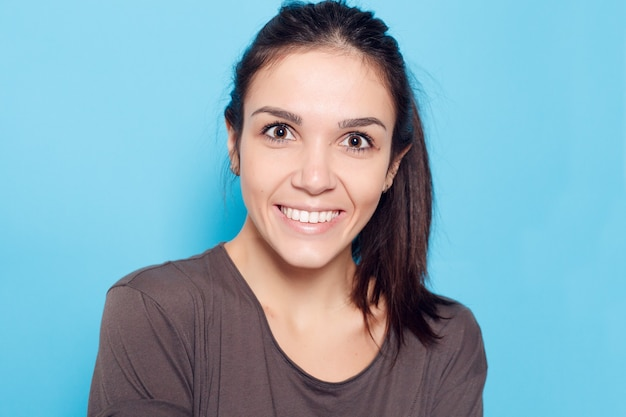 Healthy lifestyle, happiness and people concept - beautiful smiling woman on blue background.