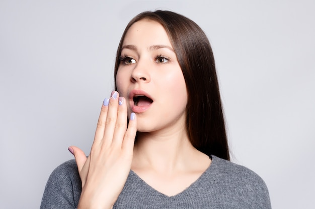 Healthy lifestyle, happiness and people concept - young beautiful cute girl showing different emotions. background for girl a concrete gray wall. laughing, smiling, anger, suspicion, fear, surprise.