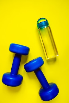Healthy lifestyle, healthy habits. detox water, fruit salad, sport equipment dumbbells on blue background top view copy space