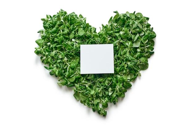 Здоровый образ жизни. сердце из листьев шпината и бумага для записей в центре рисунка. свежие листья салата