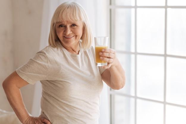 健康的な生活様式。うれしそうな幸せなポジティブな女性笑顔と窓に立っている間オレンジジュースとグラスを保持します。
