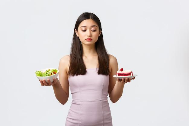 健康的なライフスタイル、レジャー、食品のコンセプト。カロリーいっぱいの甘いおいしいケーキを噛む誘惑に抵抗しようとしている美しいアジアの女の子