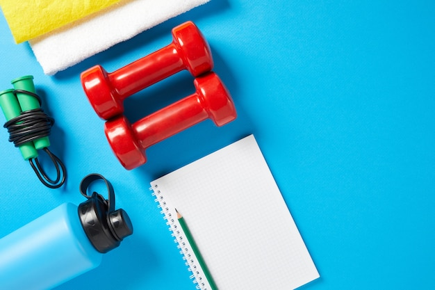 Healthy lifestyle, lose weight and sport concept. athlete's equipment: red dumbbell, sport water bottles, blank notebook, pen, jump rope on blue background. space for text. flat lay, top view